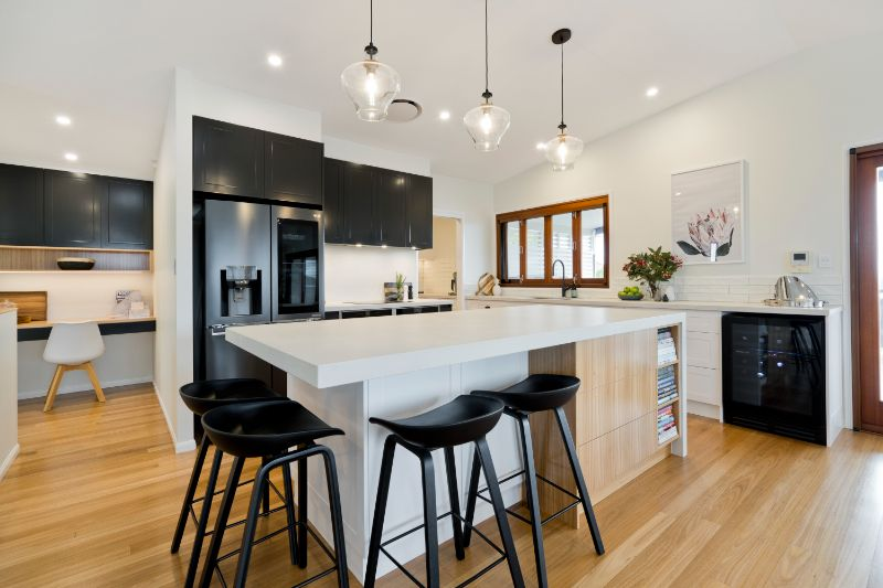 glass pendants wooden floorboards monochrome kitchen study nook wine fridge integrated