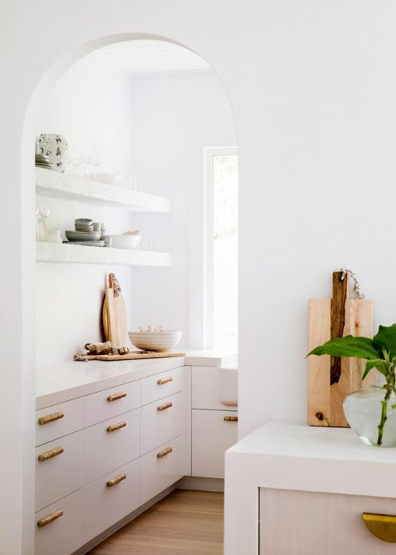 curved arched doorway unique handles brass white cabinetry